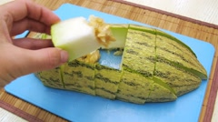 Sliced melon is on the board on table, hand takes pieces of it Stock Footage