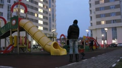 Boy with dolly camera walks around playground among buildings Stock Footage