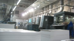 Workers work in printing machines, in foreground a pile of paper Stock Footage