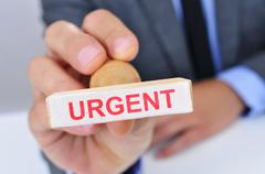 Man with a rubber stamp with the word urgent Stock Photos
