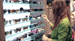 Young couple shopping in store, buy sunglasses - stock footage
