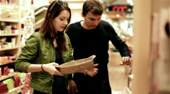 Young couple choosing dishes in shopping mall shop Stock Footage