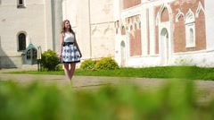 Beautiful young woman walking in a park in summer Stock Footage