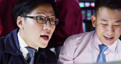4K Asian financial brokers watching the world markets in a busy trading room - stock footage