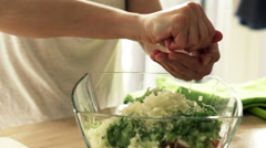 Woman squeezing juice out of lemon into salad in kitchen at home HD Stock Footage