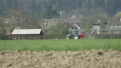 Tractor driving along the agricultural fields in the village Stock Footage