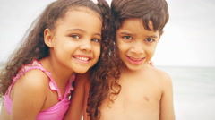Young siblings smile on a beach - stock footage