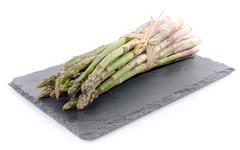 Bunch of fresh green asparagus on a slate tray - stock photo