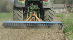 CLOSE UP SLOW MOTION: Tractor harrowing the field in spring Stock Footage