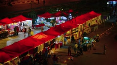 VIENTIANE, LAOS - CIRCA DEC 2013: Shoppers browse the well lighted vendor sta Stock Footage