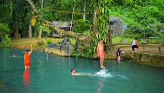 VANG VIENG, LAOS - CIRCA DEC 2013: Tourists leaping playfully into the cool, Stock Footage