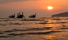 Three long-tail boats floating during sunset Stock Photos