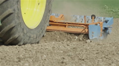 SLOW MOTION CLOSE UP: Agricultural machinery harrowing soil on field - stock footage