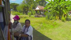 THAILAND - CIRCA DEC 2013: Female bus conductor makes way for an exiting pass Stock Footage