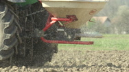 Stock Video Footage of SLOW MOTION CLOSE UP: Fertilizing field with manure with tractor