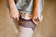 Tender undressing.  Girl in nightdress moving down her tights - stock photo