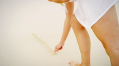 Woman writing in sand on a beach Stock Footage