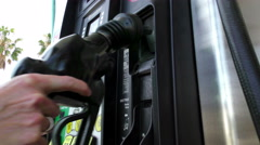 Placing Nozzle in Holder at Gas Pump - stock footage