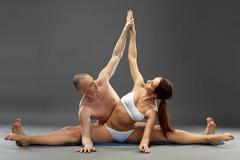 Paired yoga. Harmonious composition of athletes - stock photo