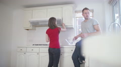 4K Happy young couple packing dishes away in the kitchen of their new home Stock Footage