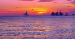 Colorful and vivid sunset at sea coast with boats sailing on horizon Stock Footage