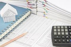 Pencil and house on notebook with calculator - stock photo