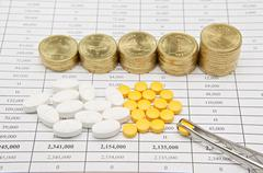 Forceps pinch pill with step pile of gold coins - stock photo