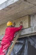 Man installing external wall insulation Stock Photos
