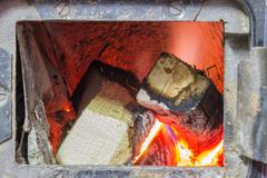 Wood stove firebox with fire and wood Stock Photos