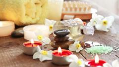 Spa still life of massage oil, towel, rocks and flowers Stock Footage