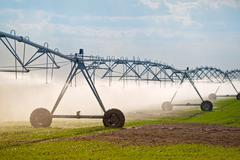 Automated Farming Irrigation Sprinklers System in Operation - stock photo