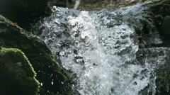 Waterfall illuminated by sunlight small drops splashes spectacular Stock Footage