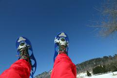 Mountaineer's legs with snowshoes for excursions on the snow - stock photo