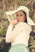 Cheerful fashionable woman in stylish hat and frock posing - stock photo