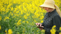 Female Farmer using Digital Tablet Computer in Rapeseed Agricultural Field Stock Footage
