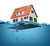 Toy house sinking underwater on a white background showing flooding concept - stock photo