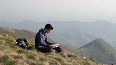 Stock Video Footage of young man reading a book in solitude in the mountains