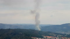 Smoke column rises from a new wildfire menacing the town of Povoa de Lanhoso Stock Footage