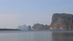 Thai longtail boat drifts along river to cliff Stock Footage