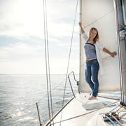 Woman staying on sailboat Stock Photos