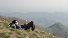 Boy reads book on top of the mountain Stock Footage