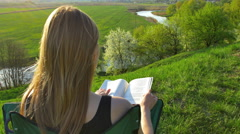 The woman read the book by picturesque landscape background. Real time capture Stock Footage