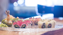 Selective focus on different delicious rolls lying in big plate Stock Footage