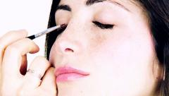 Gorgeous woman getting eyes retouched from professional makeup artist slow mo Stock Footage