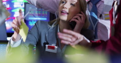 4K Portrait of female city stockmarket trader, at work in chaotic trading room Stock Footage