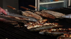 Cook cooking roasted fish on grill at a barbecue Stock Footage