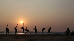 People stretching at a sandy beach in Goa at sunset. Stock Footage