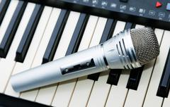 The microphone lies on the synthesizer keyboard - stock photo
