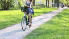 Young woman in short grey dress with long hair rides a bicycle with basket an Stock Footage