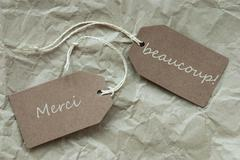 Two Labels Merci Beau Means Thank Paper Background - stock photo